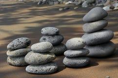 Basaltstenar på strand Arkivfoton
