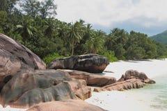 Basaltstenblock på den sandiga stranden Baie Lazare, Mahe, Seychellerna Royaltyfri Fotografi
