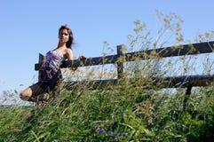 Basamento della donna vicino alla rete fissa di legno Fotografie Stock Libere da Diritti