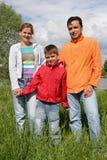 Basamento della famiglia su erba Fotografia Stock Libera da Diritti