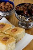 Basbousa with Almonds and Dates in Bowls Royalty Free Stock Photos