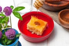 Basbousa - arabian cake with almonds and honey syrup in bowl on white wooden background Royalty Free Stock Photos