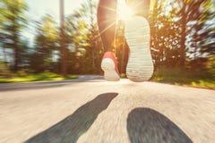 Basculador de la mujer que corre abajo del camino Imagenes de archivo