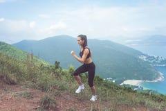 Basculador fêmea apto que exercita, correndo subida com mar e montanha no fundo Fotografia de Stock Royalty Free
