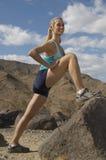 Basculador fêmea que estica na rocha Fotografia de Stock Royalty Free