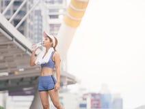 Basculador fêmea sedento que bebe a água fresca após a formação A mulher atlética nova que exercita na cidade estaciona fora fotografia de stock