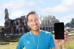 Basculador feliz que mostra Smartphone contra Colosseum fotografia de stock royalty free