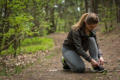 Basculador fêmea que amarra sapatas desportivas Fotos de Stock Royalty Free