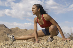 Basculador fêmea que estica nas montanhas Fotografia de Stock Royalty Free