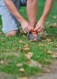 Basculador masculino que amarra laços em suas sapatas fora Fotografia de Stock