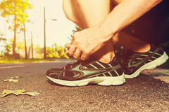 Basculador masculino que amarra seus tênis de corrida imagens de stock