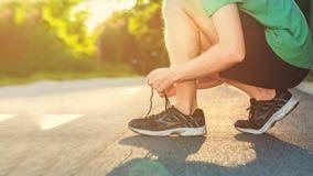 Basculador masculino que amarra seus tênis de corrida no por do sol imagens de stock