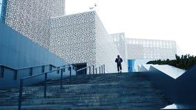 Basculador urbano en la escalera Atleta abajo de las escaleras El hombre corre encima de las escaleras Fotografía de archivo