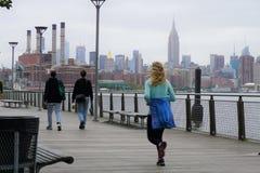Basculador y caminante en un paseo marítimo en Brooklyn con horizonte de NYC en el fondo imagen de archivo