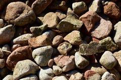 Bascule la texture approximative Fond rocailleux de roches avec des couleurs Pierres d'une plage avec la lumière du soleil image libre de droits