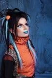 Basculez la fille avec les lèvres bleues et la coiffure punk se penchant contre le grun Image stock