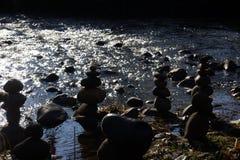 Basculez les personnes au bord du ` s de rivière avec la lumière du soleil miroitant sur l'eau Photos stock