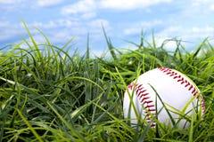 Base-ball dans l'herbe avec le ciel bleu et les nuages blancs photos stock
