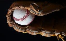 Base-ball dans la mitaine sur le noir Photographie stock libre de droits