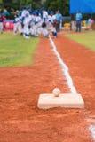Base-ball et base sur le terrain de base-ball avec des joueurs et des juges Photos stock