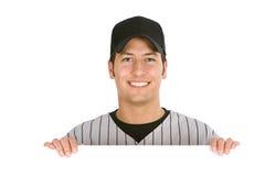 Base-ball : Joueur de sourire derrière la carte blanche Image stock