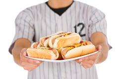 Base-ball : Joueur tenant le plat des hot-dogs Image stock