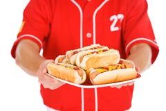 Base-ball : Joueur tenant le plat des hot-dogs pour le casse-croûte Photos libres de droits