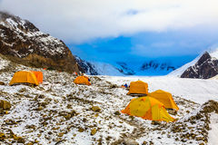 Base Camp of High Altitude Expedition. Many Orange Tents Located on Side Rock Moraine of Glacier in Severe Snow and Ice Peaks Valley Stock Images