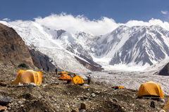 Base Camp of High Altitude Expedition. Many Orange Tents Located on Side Rock Moraine of Glacier in Severe Snow and Ice Peaks Valley Royalty Free Stock Photography