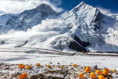 Base Camp of High Altitude Mountain Expedition. Many Orange Tents Located on Side Rock Moraine of Glacier in Severe Snow and Ice Peaks Landscape royalty free stock photos