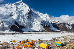 Base Camp of High Altitude Mountain Expedition. Many Orange Tents Located on Side Rock Moraine of Glacier in Severe Snow and Ice Peaks Landscape Royalty Free Stock Photography