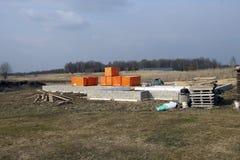 Base concrète des protections de blocs pour nouvelle une palette de maison et de peu de briques près de bois de forêt dans le wea Image libre de droits