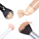 Base, crayon de crayon correcteur et poudre avec des brosses de maquillage photos stock