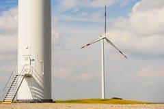 A base da turbina eólica, uma no fundo, hélice visível. Foto de Stock
