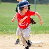 Base de corrida do menino novo segunda a primeira base Imagens de Stock