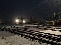 Base de la reparación en la noche del invierno snowing imagenes de archivo