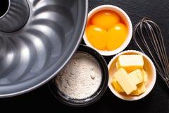 Base del burro della preparazione del forno, farina, rossi d'uovo sullo sla nero immagini stock