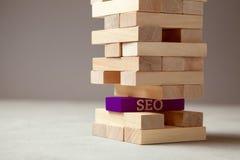 Base di SEO di riuscito sito o di un deposito online Torre di legno del blocco con il segno di seo immagini stock libere da diritti