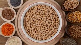 Base inteira da dieta de alimentos - várias sementes em umas bacias que alternam rapidamente em uma placa central vídeos de arquivo