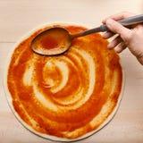 Base italiana da pizza de Spreading Sauce On do cozinheiro chefe fotos de stock royalty free