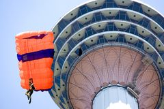 Base Jumping. Image of a daring base jumper in action. In the background is the KL Tower, at Kuala Lumpur, Malaysia Stock Photos