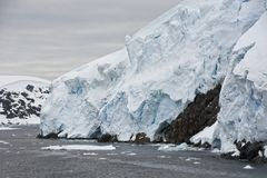 Glacier`s Edge on a Cloudy Day. Base of a mountain in Antarctica shows the edge of a glacier, with cracks and crevasses royalty free stock images