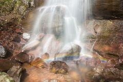 Base of a powerful waterfall splashing on the rock creating a rainbow stock photo