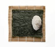 A base quadrada da alga para o sushi com uma bola de arroz em uma esteira considera imagens de stock royalty free