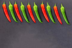 Base of red green pods of hot pepper border top frame on black background design copy space stock photo