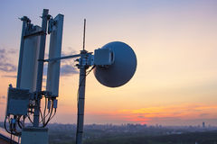 Base station with radio relay antenna on the background of a sunset over the city Stock Images