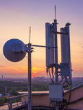 Base station with radio relay antenna on the background of a sunset over the city Royalty Free Stock Image
