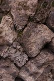 Base stone block weathered gray beige sloping cobblestone rock mountain part of the gorge wall close-up background stock photography