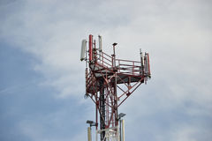 Base transceiver station (BTS) with antenna isolated on blue sky background. Telecommunications radio tower cells Royalty Free Stock Image
