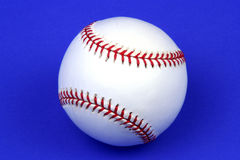 Baseball. Closeup of a baseball on a blue background Royalty Free Stock Photography